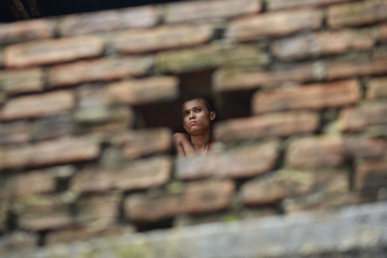 "A Myanmar Buddhist monk is pictured through a hole in a wall at a monastery where people gathered in the first ever rally to mark the ""Saffron Revolution"" in Yangon. Over a hundred people, among them dozens of monks, gathered at a Yangon monastery on September 18 to mark the ""Saffron Revolution"" which was brutally crushed by Myanmar's junta five years ago. (Ye Aung ThuYe Aung Thu/AFP/Getty Images)"