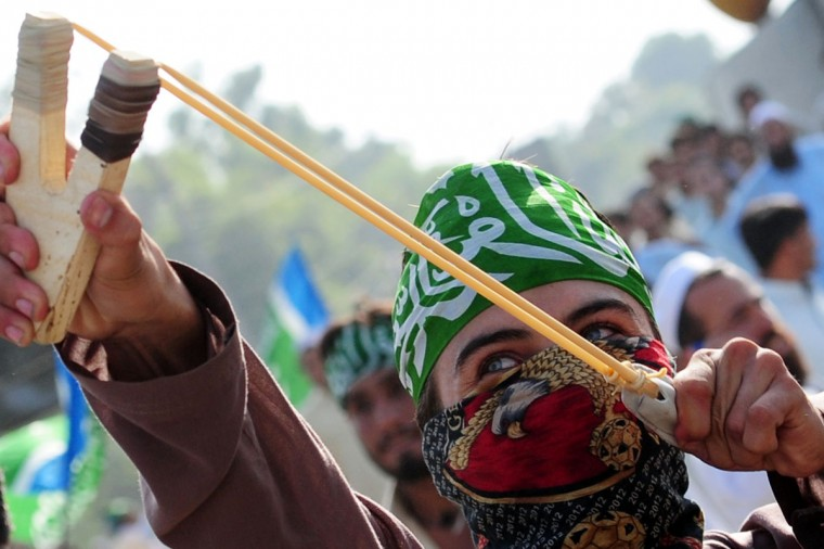 A Pakistani activist of the hard line Sunni party Jamaat-e-Islami (JI) uses a sling shot to hurl stones at the police during a protest against an anti-Islam movie in Peshawar on September 18, 2012. (A. Majeed/AFP/Getty Images)