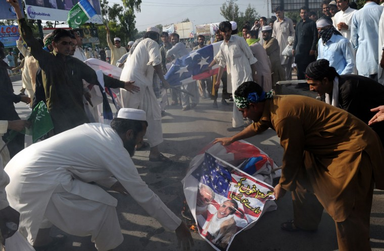 Pakistani activists of the hard line Sunni party Jamaat-e-Islami (JI) torch a US flag along with the portrait of US President Barack Obama and Florida pastor Terry Jones during a protest against an anti-Islam movie in Peshawar on September 18, 2012. (A. Majeed/AFP/Getty Images)