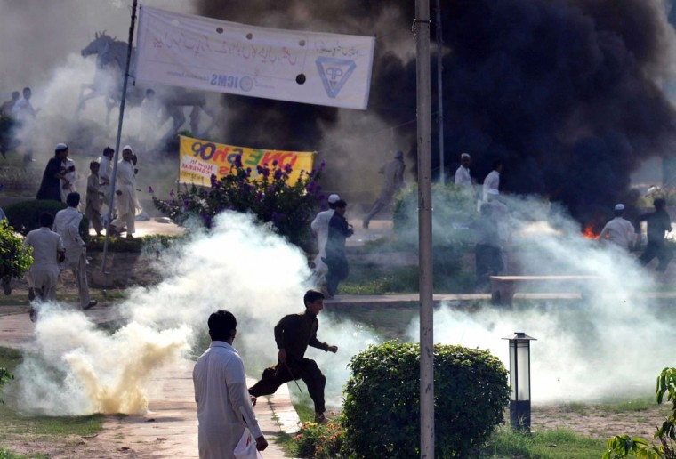 Pakistani activists of the hard line Sunni party Jamaat-e-Islami (JI) dispurse after police fired tear gas during a protest against an anti-Islam movie in Peshawar on September 18, 2012. (A. Majeed/AFP/Getty Images)