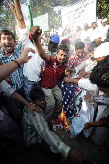 People burn an American flag as they protest against an anti-Islam film made in the United States, on September 18, 2012 near the American consulate, in Chennai. About 5000 people from all over South India have gathered in front of USIS (United State Information Service) complex and burnt an American flag with a picture of U.S. President Barrack Obama. (Stringer/AFP/Getty Images)