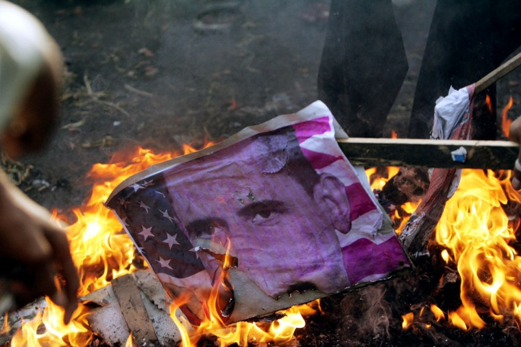 An American flag with a picture of U.S. President Barrack Obama is burnt buy Indian muslims as they protest against an anti-Islam film made in the United States, on September 18, 2012 near the American consulate, in Chennai. (Stringer/AFP/Getty Images)