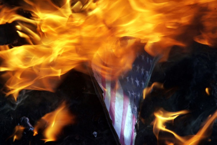 An American flag with a picture of U.S. President Barrack Obama is burnt buy Indian muslims as they protest against an anti-Islam film made in the United States, on September 18, 2012 near the American consulate, in Chennai. About 5000 people from all over South India have gathered in front of USIS (United State Information Service) complex and burnt an American flag with a picture of U.S. President Barrack Obama. (Stringer/AFP/Getty Images)