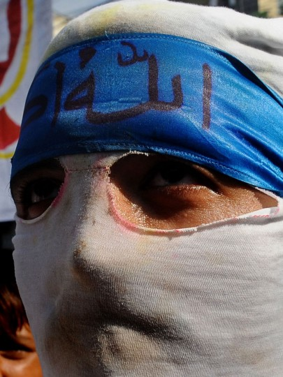 A masked Pakistani activist of the hard line Sunni party Jamaat-e-Islami (JI) marches during a protest against an anti-Islam movie near the US consulate in Lahore on September 19, 2012. The Pakistan government has declared Friday a national holiday in honor of the Muslim prophet Mohammed and called for peaceful protests against a US-made film deemed insulting to Islam. (Arif Ali/AFP/Getty Images)