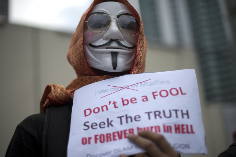 "A protestor wearing a scarf holds a placard in front of the US embassy during a rally against an anti-Islam film, ""Innocence of Muslims"" and the publication of caricature of the Holy Prophet Muhammad by a French magazine in Kuala Lumpur. Hundreds of protestors marched in a peaceful rally shouted slogans against United States in front of the embassy building. (Saeed Khan/AFP/Getty Images"