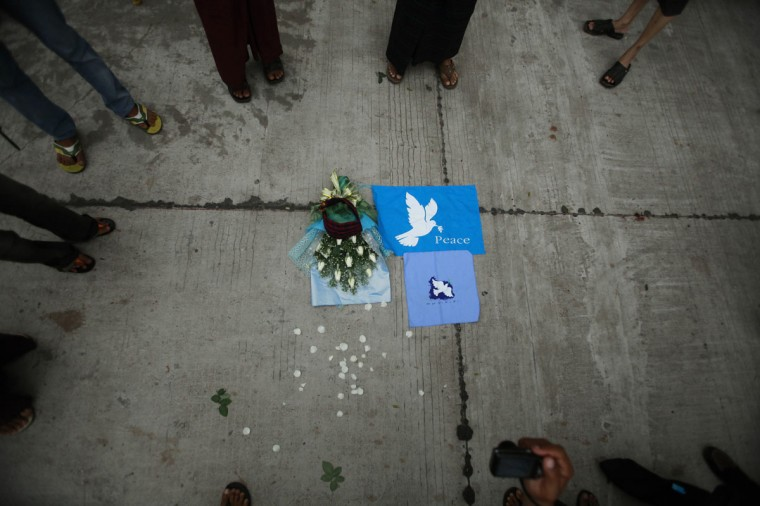 A bouquet of flowers and pictures of doves calling for peace lie on the ground as protesters gather before being blocked by police from heading to Naypyidaw to stage a rally, forcing them to join the Yangon peace rally instead in Myanmar's former capital Yangon. Hundreds of people gathered in Yangon on September 21 calling for an end to the festering conflict between Kachin ethnic minority rebels and Myanmar's army. (Ye Aung Thu/AFP/Getty Images)
