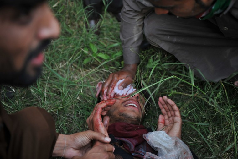 Pakistani Muslim demonstrators help an injured colleague during their attempts to reach the US embassy during a protest against an anti-Islam film in Islamabad. (Aamir Qureshi/AFP/Getty Images)