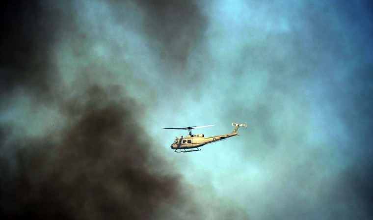 A Pakistani security survilience helicopter patrols through smoke clouds during an anti-US demonstration against an anti-Islam film in Islamabad. A Pakistani policeman and a driver for a television station were shot dead during a day of protests condemning a film made in the United States and deemed insulting to Islam, officials said. (Aamir Qureshi/AFP/Getty Images)
