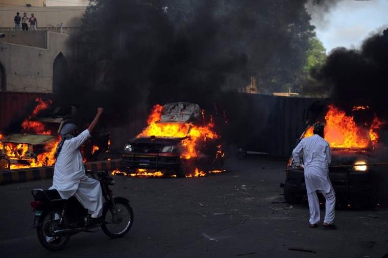 A Pakistani Muslim demonstrator (R) hits a burning police vehicle during a protest against an anti-Islam film in Karachi. At least 13 people died and nearly 200 were wounded in Pakistan during violent protests on Friday condemning a US-made film insulting Islam, defying a government call for only peaceful demonstrations, officials said. (Asif Hassan/AFP/Getty Images)