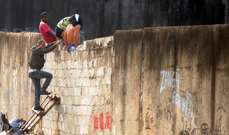 Crack addicts jump a wall to escape from members of the municipal Social Assistence department of Rio de Janeiro, during an operation at the railroad area of Madureira, 25 Km from Rio's downtown. (Antonio Scorza/AFP/Getty Images)