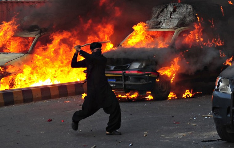 A Pakistani Muslim demonstrator brandishes a stick near burning police vehicles during a protest against an anti-Islam film in Karachi. (Asif Hassan/AFP/Getty Images)
