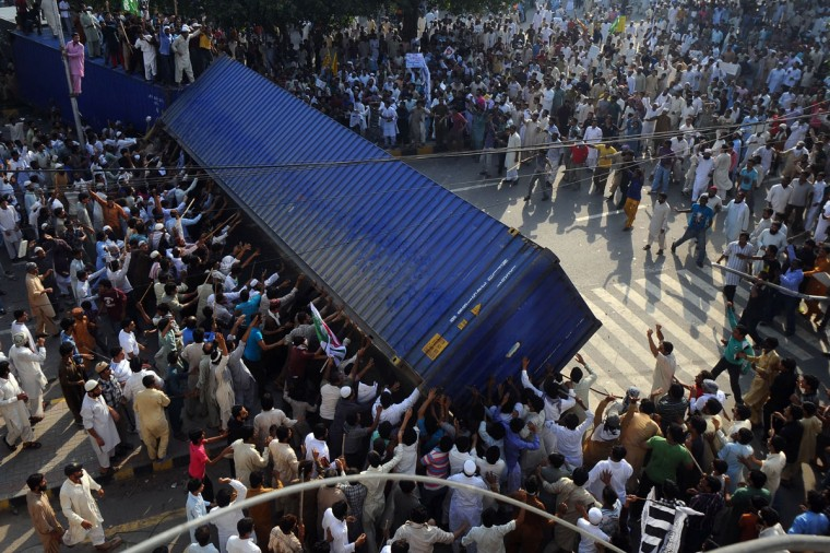 Pakistani Muslim demonstrators topple a freight container, placed by police to block a street during a protest against an anti-Islam film in Lahore. (Arif Ali/AFP/Getty Images)