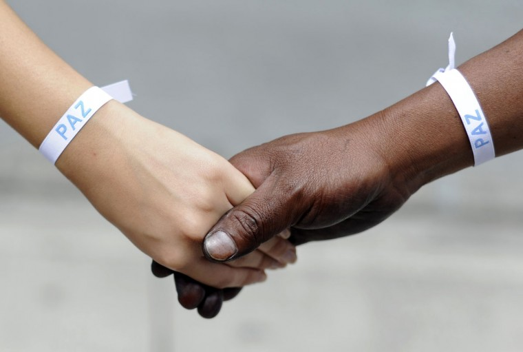 A student (L) and a shoe shiner hold hands during in a human chain held in Guatemala City, during celebrations of the UN International Day of Peace. (Johan Ordonez/AFP/Getty Images)