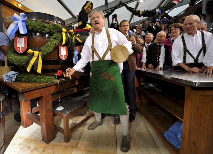 "Munich mayor Christian Ude taps the first keg of beer with the traditional ""O'zapft is!"" (It's tapped!) to kick off the Oktoberfest beer festival in Munich, Germany. (Frank Leonhardt/AFP/Getty Images)"