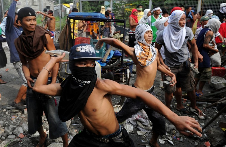 Residents throw stones and beer bottles at a demolition team and anti-riot police during an operation at an informal settlers area to give way for a local government project in Manila on September 24, 2012. (Noel Celis/AFP/Getty Images)