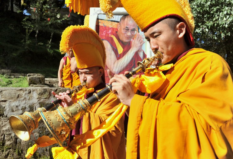 Tibetans dressed in religious attire play musical instruments as they lead a procession with the portrait of Tibetan spiritual leader The Dalai Lama (C) during the ceremonial start of the Second Special General meeting of Tibetans in Dharamshala. The four-day second Special General meeting of Tibetans which begins September 25 will be discussing the critical issues of recent self immolations by Tibetans in Tibet, and taking up the Tibet issue with new Chinese leadership. (Manjunath Kiran/AFP/Getty Images)