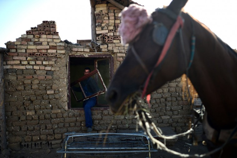 A Roma man collects material from his home before it gets demolished by a bulldozer in a Roma suburb in the town of Maglizh. Thirty-two illegally built Roma houses were destroyed in the periphery of the central Bulgarian town of Maglizh. (Dimitar Dilkoff/AFP/Getty Images)