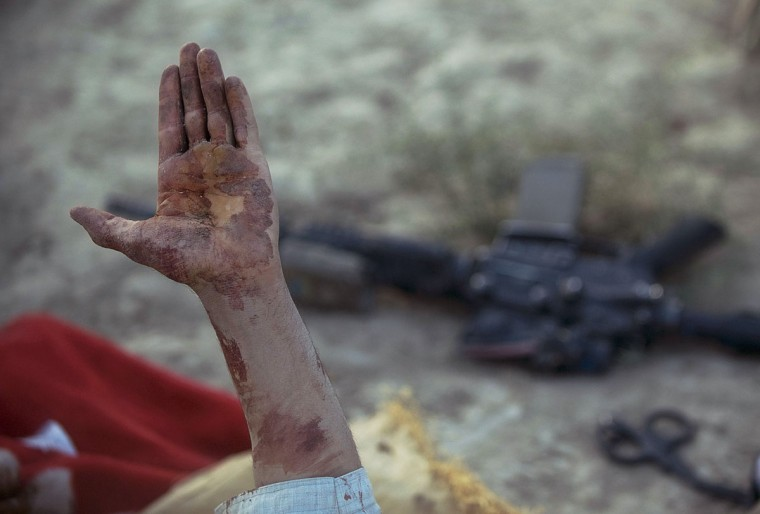 An Afghan villager holds up a blood stained hand to US military soldiers from the 3rd platoon, C-company, 1-23 infantry, before they use a ballistics kit to test for explosive residue on his hands after he was shot because he was suspected of being an insurgent and planting a roadside bomb, in Genrandai village at Panjwai district, Kandahar on September 24, 2012. The wounded man denied being Taliban, an association with which consequently leads to incarceration for the suspect and his family, saying he had been working at a grapevine when he was shot. (Tony Karumba/AFP/Getty Images)