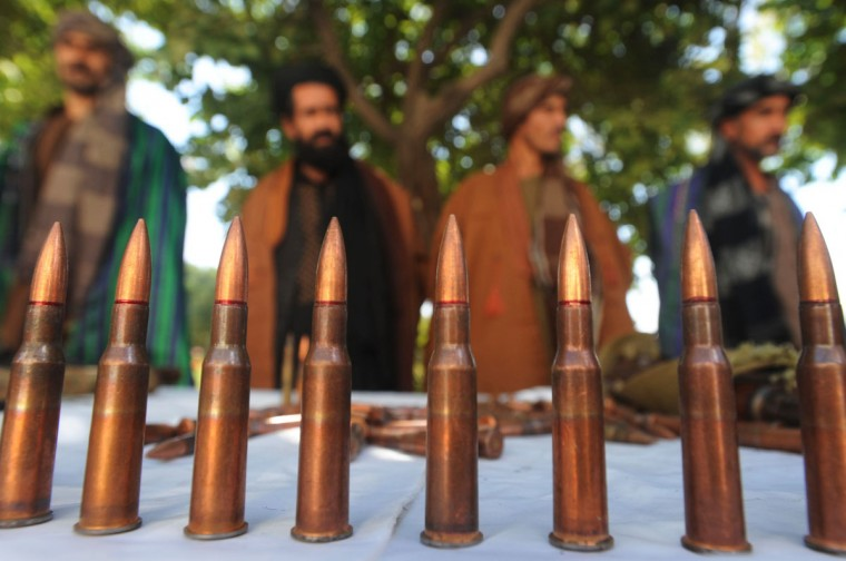 "Four of seven members of a Taliban group pose for a photo in front of ammunition and guns they turned in to authorities near Herat. The Afghan Taliban dismissed NATO figures showing a decrease in insurgent attacks, saying the statistics reflect troop withdrawals and a ""cowardly"" avoidance of contact. (Aref Karimi/AFP/Getty Images)"