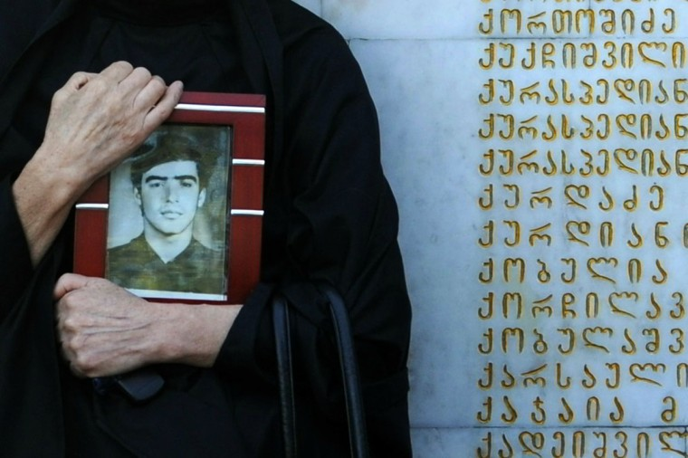 A woman holds a portrait as she mourns at a memorial to those killed during the 1992-1993 Georgia-Abkhazia armed conflict at a ceremony marking the annual anniversary of the event in Tbilisi, on September 27, 2012. (Vano Shlamov/AFP/Getty Images)