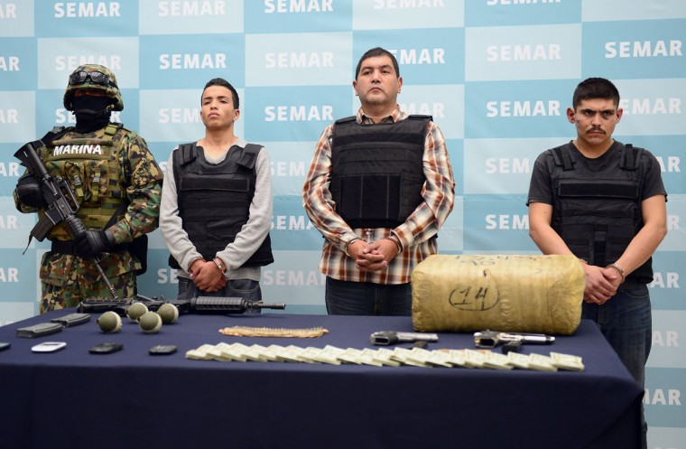 "Ivan Velazquez Caballero, aka ""Z 50"" or ""El Taliban"" (2nd-R), senior leader in the Zetas drug cartel and member of the Gulf cartel, is presented to the press at the Mexican Navy headquarters in Mexico City, on September 27, 2012. Velazquez Caballero was on a list of Mexico's most wanted drug traffickers, with an offer of some $2.3 million for information leading to his capture. (Alfredo Estrella/AFP/Getty Images)"