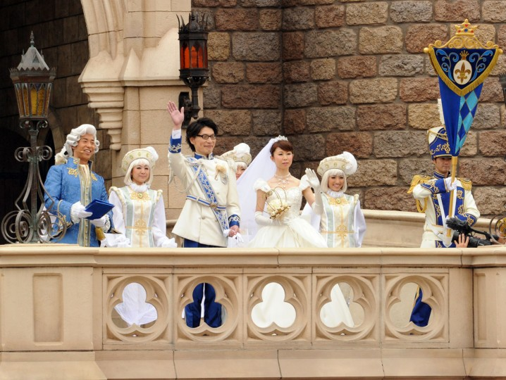 Newly wedded bride Mayumi Kagoshi (3rd R) and her groom Takayuki Abiko (3rd L) wave from the balcony of the Cinderella castle after their wedding at the castle of the Tokyo Disneyland in Urayasu, suburban Tokyo. Abiko and Kagoshi became the first couple to hold a wedding ceremony in Disney's theme park in Japan. (Yoshikazu Tsuno/AFP/Getty Images)