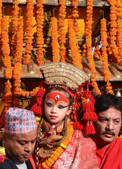 "A young Nepalese girl revered as the living goddess ""Kumari"" is carried to the golden chariot on the main day of the Hindu Indra Jatra festival at Basantapur Durbar Square in Kathmandu. The week-long festival celebrates Indra, the king of gods and the god of rains, when the Kumari living goddess is carried in a palanquin during a religious procession through parts of the Nepalese capital. (Prakash Mathema/AFP/Getty Images)"