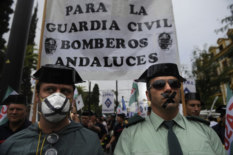 Spanish civil guards with their mouths sealed with tape attend a demonstration of public service workers against government spending cuts on Sept. 29 in Seville. Spain's government said it would freeze public sector pay, which has not risen since it was cut by five percent in 2010 and which suffered an effective seven-percent fall this year with the cutting of the end-of-year bonus. (Cristina Quicler/AFP Getty Images)