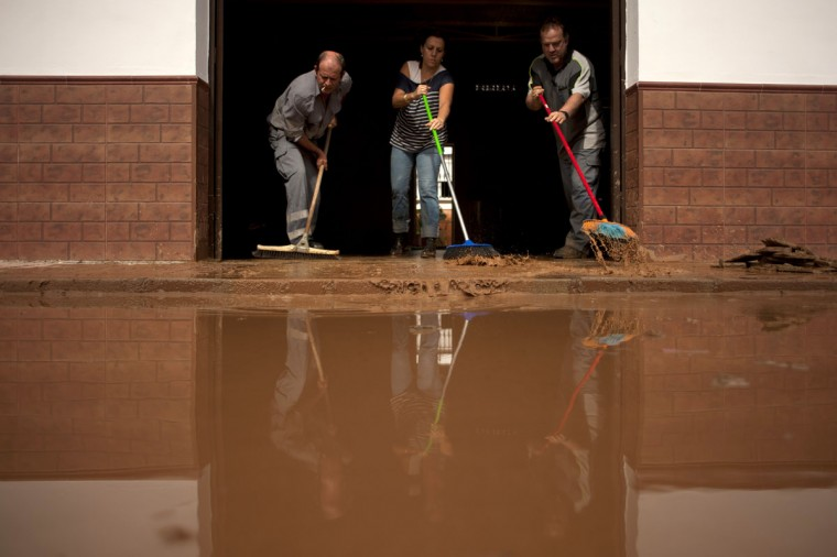 People clean the entrance of their flooded home in Bobadilla, near Malaga, Spain. At least eight people, including a young girl and an elderly woman, have died in Spain as a result of floods brought on by downpours, regional officials said. Some 500 people remained evacuated from their homes in the area. (Jorge Guerrero/AFP/Getty Images)