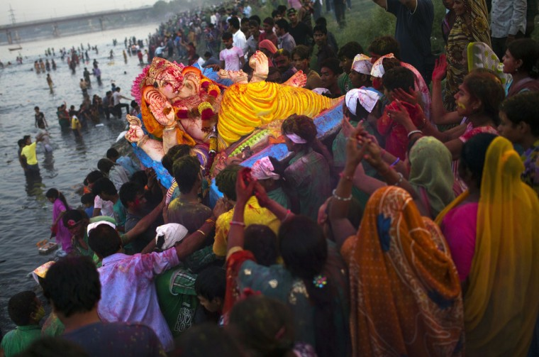 Indian Hindu devotees prepare to immerse an idol of the elephant-headed Hindu god Lord Ganesha into the Yamuna river in New Delhi. During the ten-day Ganesh Festival, Hindu devotees bring home idols of Lord Ganesha and offer prayers in temporary temples in order to invoke his blessings for wisdom and prosperity, culminating with the immersion of the idols in bodies of water. (Andrew Caballero-Reynolds/AFP/Getty Images)