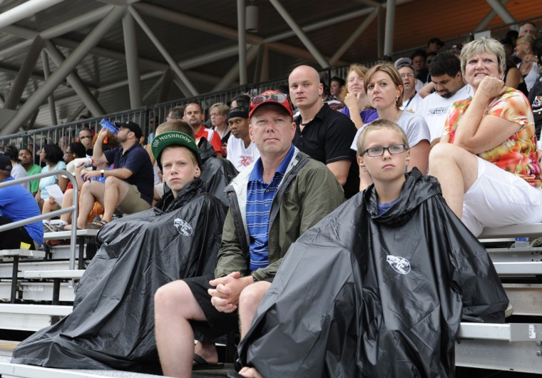 Enjoying their 1st Grand Prix of Baltimore, (L) Noah Nipp, 14, (Dad) Bob Nipp, and (R) Aaron Nipp, 11, from Newport News Virginia, break out the rain gear shortly after the start of the race. (Jeffrey F. Bill/Baltimore Sun)