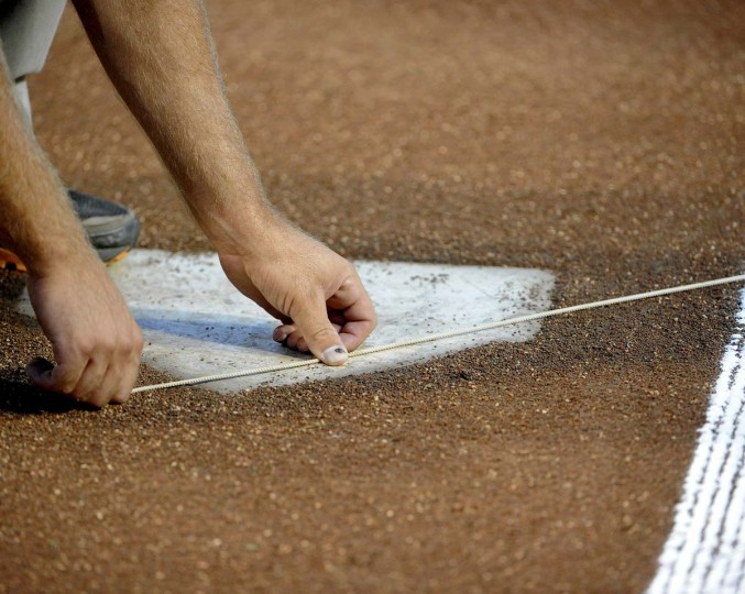 Cords are being stretched from home plate down the foul lines so the chalk can be applied in straight lines down the base paths (Gene Sweeney Jr. /Baltimore Sun)