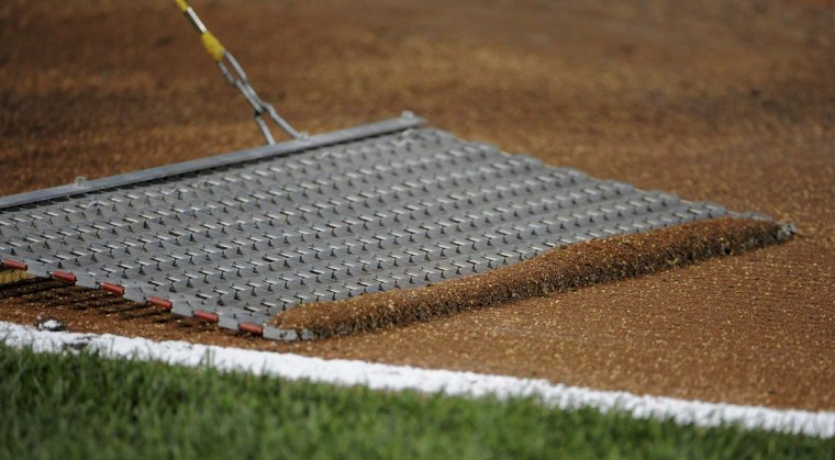"The infield dirt is ""screened"" by a grounds crew member before the start of the ball game. (Gene Sweeney Jr. /Baltimore Sun)"