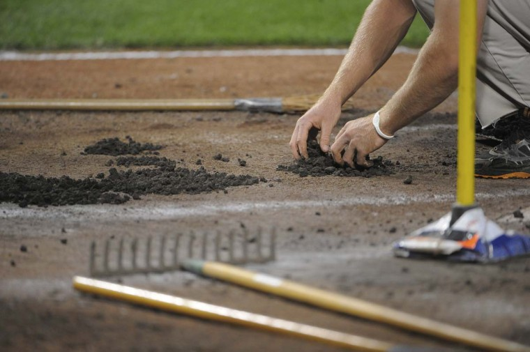 Brian Holtrop repairs the divots in the batter's box around home plate before a game against the Toronto Blue Jays at Camden Yards. (Gene Sweeney Jr. /Baltimore Sun)