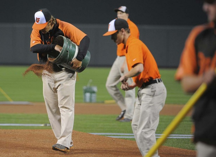 "Thomas Kirsch spreading ""top dressing"" on the pitchers mound. (Gene Sweeney Jr. /Baltimore Sun)"
