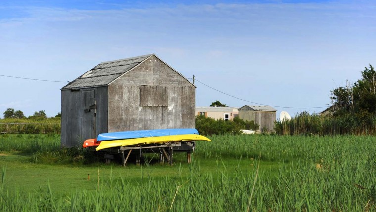 Colorful canoes rest outside a shed in the town of Tylerton on Smith Island. (Barbara Haddock Taylor/Baltimore Sun)