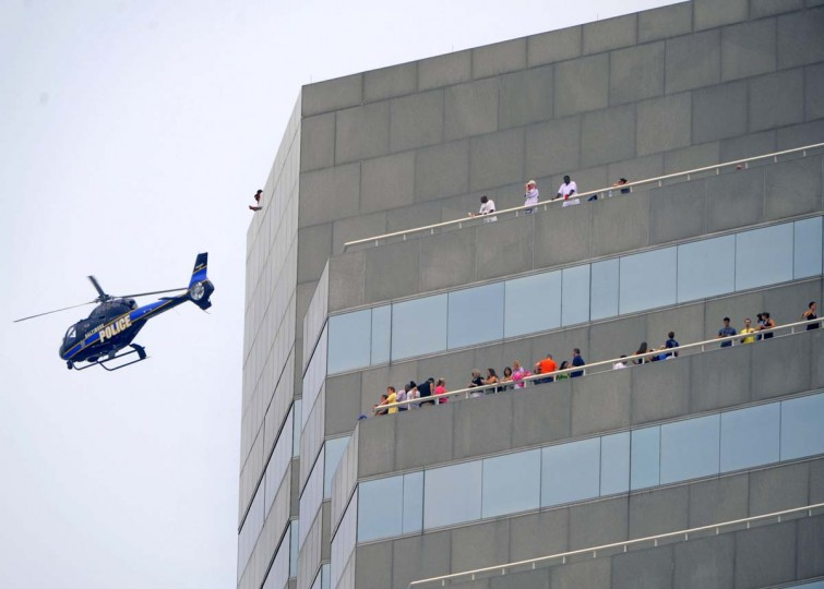 A helicopter scans over the area above people on the rooftop of a building, who watch race car drivers tackle the streets in the Grand Prix of Baltimore. (Karl Merton Ferron/Baltimore Sun)