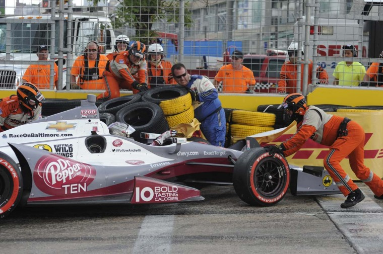 The track crew try to dislodge Marco Andretti's car from the tires in turn one during the Baltimore Grand Prix. (Jerry Jackson/Baltimore Sun)