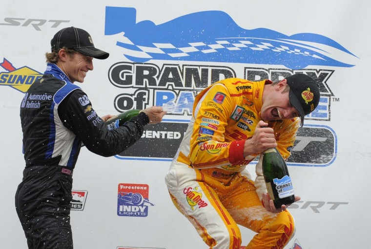 L-R Ryan Briscoe the second place finisher showers first place finisher, Ryan Hunter-Reay in the winners circle. (Lloyd Fox/Baltimore Sun)
