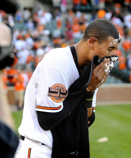 """Manny Machado wipes shaving cream from his face after he was """"pied"""" by teammate Adam Jones. Machado hit the game-winning walk-off single"""
