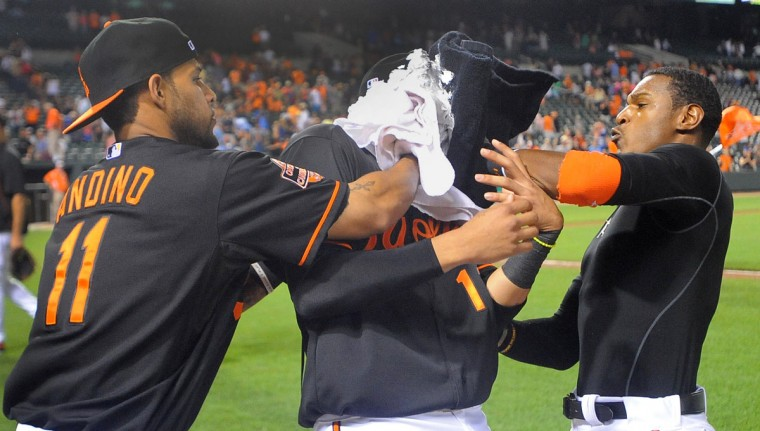 "Aug. 10, 2012: Robert Andino, left, and Adam Jones ""pie"" teammate Manny Machado in the face after Machado hit his first two career home runs in a win over the Royals. (Gene Sweeney Jr./Baltimore Sun Photo)"