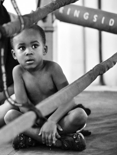 Yusuf Robinson, 4, is too young to put on the gloves, but he watches sparring in the ring at the UMAR Boxing Program, Inc. where his older siblings train. (Kim Hairston/Baltimore Sun)