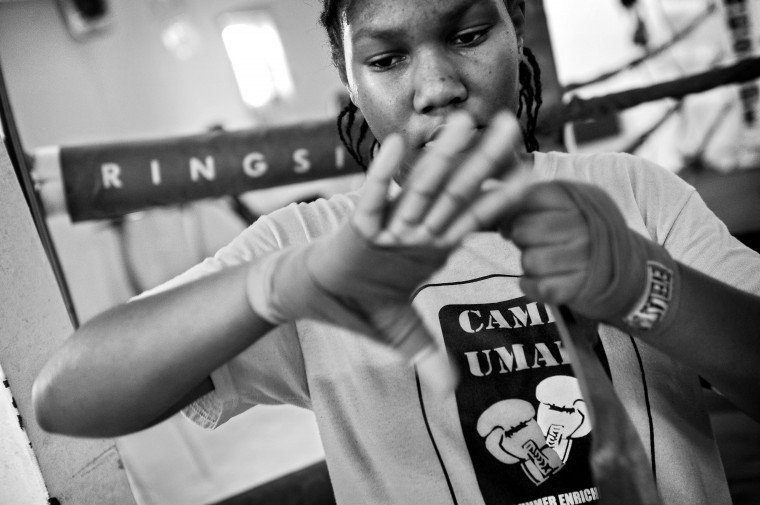 Zoria Curry, 12, wraps her hands before working out in the ring. Zoria and her brother, Kyron Curry, 10, train in the UMAR Boxing Program, Inc. Children 13 and under are required to work on their academics in UMAR's computer lab before going into the gym. (Kim Hairston/Baltimore Sun)