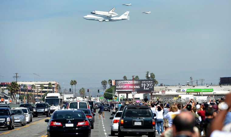 People stand along Aviation Blvd. as the space shuttle Endeavour lands at LAX Friday, September 21, 2012 in Los Angeles, California. (Wally Skalij/Los Angeles Times)