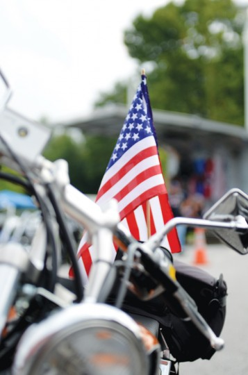 An American flag is stuck into the back of a motorcycle at the 2012 Patriot Day Ride, which honored those who died in the Sept. 11, 2001 terrorist attacks. (Jon Sham/Patuxent Homestead)