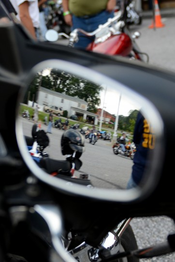 Bikers pulling into the parking lot of Chesapeake Harley-Davidson for the Patriot Day Ride are seen reflected in the mirror of a motorcycle. (Jon Sham/Patuxent Homestead)