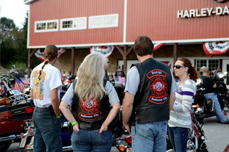 From left, Jeff Williams, of Towson, Donna Walsh and her husband Nick Walsh, of Parkville, and Williams' daughter Cara Williams look at the motorcycles in the lot. (Jon Sham/Patuxent Homestead)