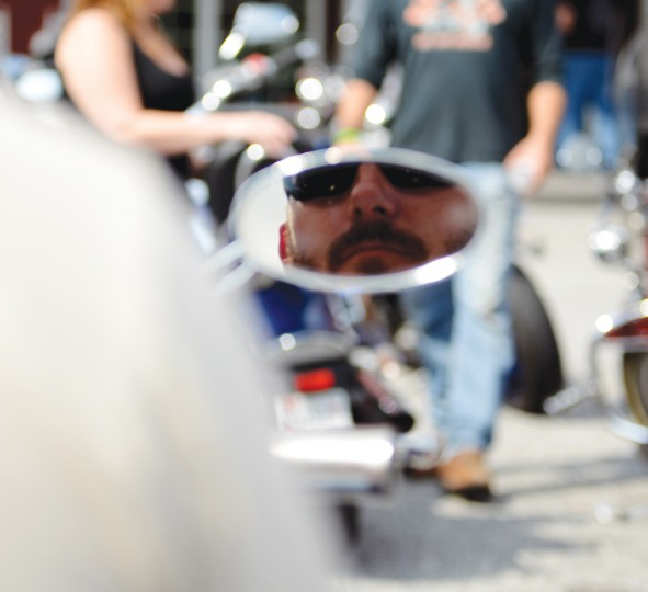 Bill Heise, of Dundalk, can be seen reflected in the right mirror of his motorcycle as he sits on it before the Patriot Day Ride. (Jon Sham/Patuxent Homestead)