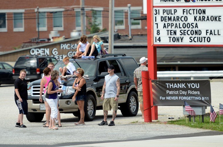 Supporters wait in the parking lot of a strip mall on Putty Hill Road where McAvoy's, the destination, awaits the riders. (Jon Sham/Patuxent Homestead)