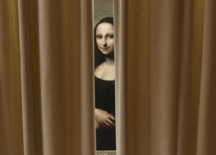 "A painting attributed to Leonardo da Vinci and representing Mona Lisa is pictured behind a curtain during a preview presentation in a vault in Geneva. The Mona Lisa Foundation, a non-profit organization based in Zurich, will present September 27, a painting and historical, comparative and scientific evidence, which demonstrate that there have always been two portraits of the Mona Lisa by Leonardo da Vinci, the ""Earlier Version"", made 10 years earlier than the ""Joconde"" that is displayed in Le Louvre in Paris. (Denis Balibouse/Reuters)"